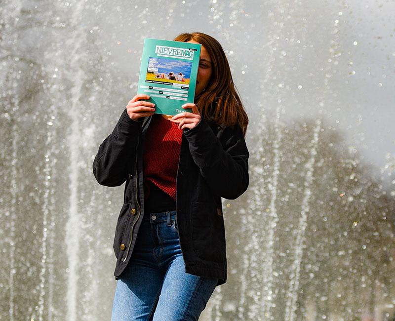 Femme tenant Nièvre Mag devant une fontaine